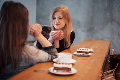 Toned picture of best friends having date in cafe or restaurant. Beautiful girls talking or communicating while drinking. Coffee Stock Image
