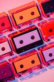 Toned picture of colorful retro audio cassettes. On pink background stock image