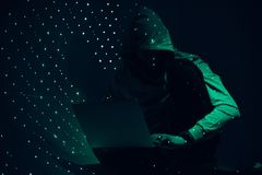 Toned picture of silhouette of hacker in hoodie. Using laptop royalty free stock photo