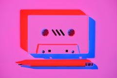 Toned pink picture of retro audio cassette and pencil. On tabletop royalty free stock photos