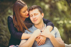 Toned portrait of beautiful woman hugging boyfriend at park Royalty Free Stock Photography