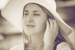 Toned portrait of beautiful woman in white hat posing on beach Stock Image