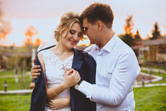 Toned portrait of careful groom embracing bride in park at sunse Stock Photos