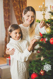 Toned portrait of cheerful mother decorating Christmas tree with Stock Image