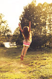 Toned portrait of cute Little girl is dancing in nature at summer sunset. Stock Photos