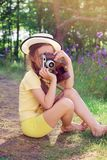 Toned portrait of Cute little girl in retro outfit taking pictures with old film camera. royalty free stock photography