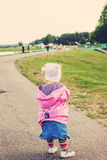 Toned portrait of Cute Little kid walking away on the road ahead Royalty Free Stock Image
