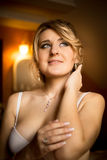 Toned portrait of elegant bride in lingerie posing at hotel room Royalty Free Stock Photo