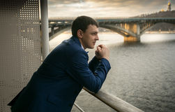 Toned portrait of elegant man in suit looking on the river Royalty Free Stock Images