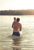 Toned portrait of Father and Daughter Playing Together at the lake. Royalty Free Stock Images