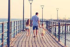 Toned portrait of Father and his little daughters walking at sunset Stock Photography