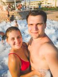 Toned portrait of happy young couple making selfie portrait of the soap foam disco party at sea beach royalty free stock photo