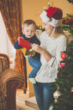 Toned portrait of happy mother giving Christmas present to her c. Toned portrait of happy young mother giving Christmas present to her cute baby boy at living Stock Photo