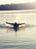 Toned portrait of man Swimming at sunset. Royalty Free Stock Image