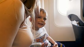 Toned portrait of young mother kissing her toddler son in airplane during first flight. Toned portrait of mother kissing her toddler son in airplane during first royalty free stock images
