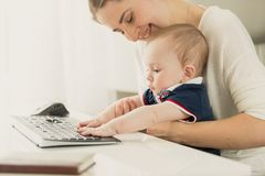 Toned portrait of smiling young mother teaching her baby son using computer at home office. Portrait of smiling young mother teaching her baby son using computer Royalty Free Stock Images