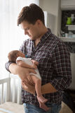 Toned portrait of young father holding newborn baby on hands Royalty Free Stock Image