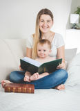 Toned portrait of young mother and her baby boy posing with big. Toned portrait of happy young mother and her baby boy posing with big book royalty free stock photography