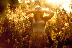 Toned portrait of young woman walking at golden field in sun ray Stock Images