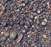 Toned round sea stones on the beach of Santorini island  Royalty Free Stock Image