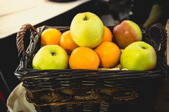 Toned shot of basket full of oranges and green apples Stock Photos