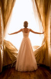 Toned shot of beautiful bride posing at window in hotel room Stock Images