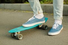 Penny skateboard commute hipster transport solutions. Toned shot of the blue canvas shoe standing at the blue plastic penny board outdoors. Concept of the modern Royalty Free Stock Photography
