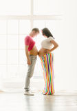 Toned shot of happy young pregnant couple touching by stomachs Stock Photo