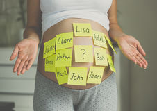 Toned shot of pregnant woman with child names on belly Royalty Free Stock Image