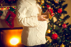 Toned shot of pregnant woman posing with Christmas gift box. Toned photo of pregnant woman posing with Christmas gift box stock photography