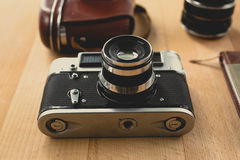 Toned shot of retro camera with portrait lens lying on wooden de. Toned shot of retro manual camera with portrait lens lying on wooden desk stock images