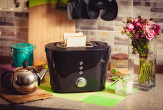Toned shot of toaster with fresh brad on decorated kitchen Royalty Free Stock Images