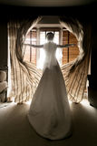 Toned shot of young bride opening curtains at hotel room Stock Photography