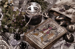 Toned still life with black candle, runes and the tarot cards Stock Image
