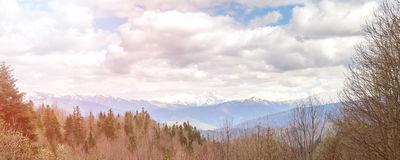 Toned sunny panorama of the cloudy sky, forests and mountains in the Caucasus Stock Photo