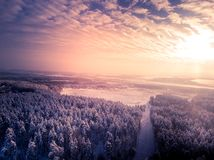 Toned. Village near field. Winter forest around. Cloudy sky and sun. Aerial view.  royalty free stock photos