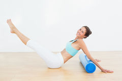 Toned woman doing the boat pose in fitness studio stock image