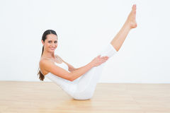 Toned woman doing the boat pose in fitness studio Royalty Free Stock Photo