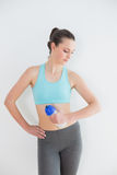 Toned woman holding water bottle against wall Stock Photo