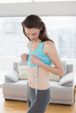 Toned woman measuring chest in fitness studio Stock Images