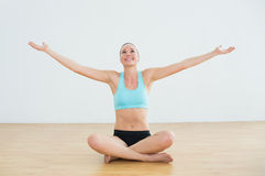 Toned woman sitting with arms outstretched in fitness studio Stock Photography