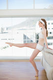 Toned woman stretching leg in fitness center Stock Photos