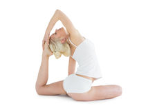 Toned young woman doing the pigeon pose Stock Image