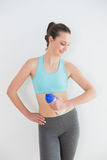 Toned young woman holding water bottle against wall Stock Photography