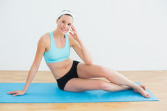 Toned young woman sitting on yoga mat Stock Photography