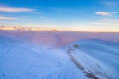 Toneel alpien landschap, wolken op het licht van de de piekenzonsondergang van de vallei arisign berg, de wintersneeuw stock afbeeldingen