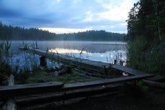 Toneel en idyllisch meerlandschap met houten voetgangersbrug en mist bij sommeravond stock foto's
