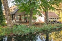 Toneel Nederlandse oude boerderij dichtbij een kanaal in Gouda, Nederland stock afbeelding