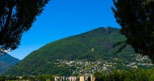 Toneelberg met een bos en huizen in de stad van Ascona, Zwitserland Royalty-vrije Stock Foto's