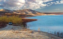 Toneeldielandschap van een auto over een meer tegen bergen wordt geparkeerd stock fotografie